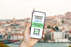 Coronavirus vaccination certificate or vaccine passport for travellers concept. COVID-19 immunity e-passport in the smartphone mobile app for international travelling. Blurred  city background