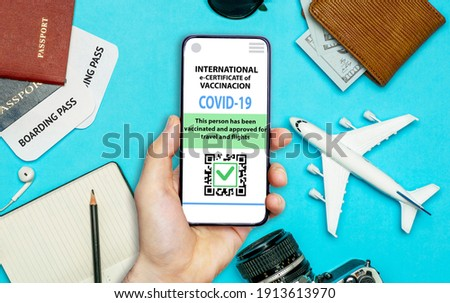 Coronavirus vaccination certificate or vaccine passport for travellers concept. COVID-19 immunity e-passport in the smartphone mobile app for international travelling. Blue background with toy plane