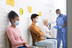Coronavirus Vaccination. Diverse Patients People Waiting For Covid-19 Vaccine Sitting In Queue In Hospital Waiting-Room. Corona Virus Prevention, Medical Immunization Campaign. Selective Focus