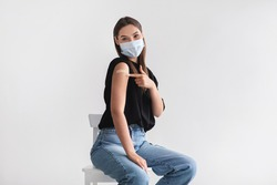 Coronavirus vaccination saves lives. Young woman in face mask pointing at adhesive bandage on her arm, getting vaccinated against covid-19 on light background. Immunization for infectious disease