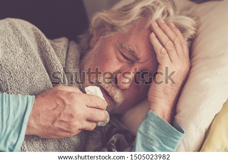 Coronavirus warning Old people senior man with winter seasonal illness fever cold problems drinking a pharmacy medicine or hot tea to go healthy - concept of mature retired with disease