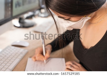 Coronavirus. Woman at the office sick with mask for corona virus. Woman take notes at office desk with computers. Business women wear masks to protect and take care of their health in the office.