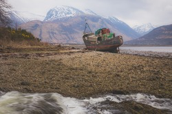 Corpach shipwreck, an abandoned vintage fishing boat, near Fort William in the Scottish Highlands with Ben Nevis mountain in the background.