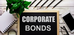 CORPORATE BONDS written on a black background near pencils, a smartphone, a white notepad and a green plant in a pot. Investment concept