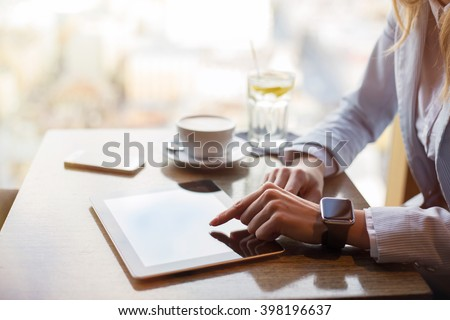 Corporate business woman working on tablet at cafe