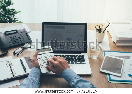 Corporate businessman working at office desk, he is using a calculator, point of view shot