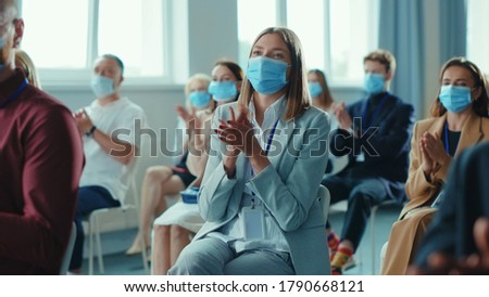 Corporate diverse business people clapping hands at successful conference. Group of happy business people in face masks sitting together on meeting seminar. Quarantine. Workspace.
