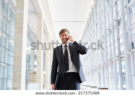 Corporate executive smiling at the camera while talking on his phone and walking down a corridor