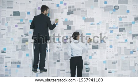 Corporate executives planning their business strategy: they are analyzing many financial reports and charts hanging on a wall