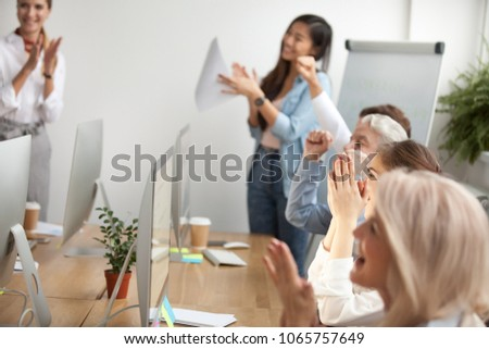 Corporate group of excited smiling friendly people clapping hands celebrating success together in office, staff or business team applauding as concept of appreciation, welcoming or congratulations