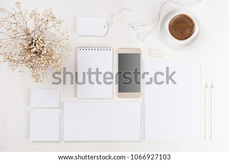 Corporate identity set of blank white stationery, telephone, coffee, flowers on soft white wood board. Template for branding, presentations and portfolios.
