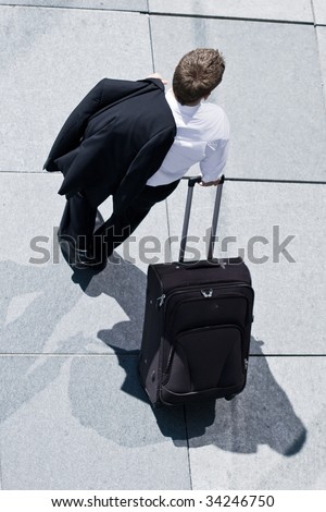 Corporate Man With Rolling Luggage Holding His Jacket - stock photo