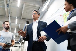 Corporate manager taking a tour in a factory and communicating with production line workers.