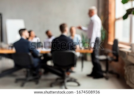 Corporate Meeting Concept, Blurred Background. Unrecognizable Businessman Giving Speech During Meeting With Coworkers In Modern Office.