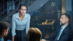 Corporate Meeting Room: Confident and Beautiful Female Executive Director Decisively Leans on the Conference Table and Delivers Report to a Board of Executives about Company's Record Breaking Revenue