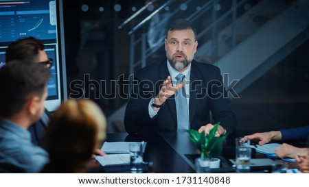 Corporate Meeting Room: Sitting at the Conference Table Charismatic Director Talks Enthusiastically and Gesticulates Energetically proving His point to Investors, Lawyers, Executives Сток-фото ©