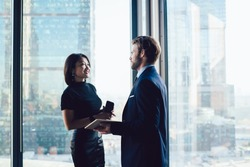 Corporate multicultural employees standing near window in office interior and talking about work, two successful cheerful business colleagues conversating and sharing ideas. Workers discussing ideas