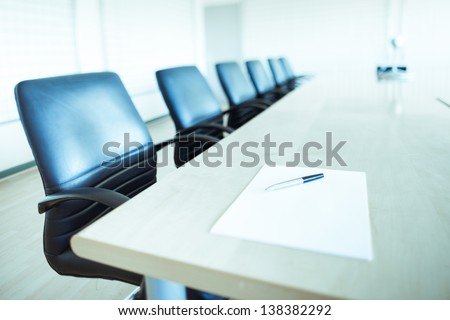 Corporate Office Chairs In A Boardroom With Pen And Paper