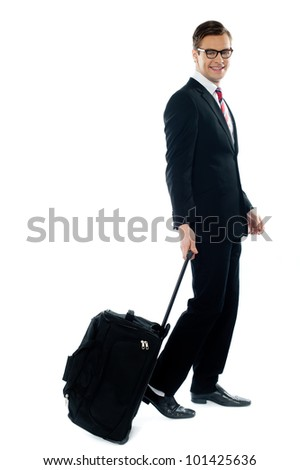 Corporate person leaving for business meeting as he drags his luggage