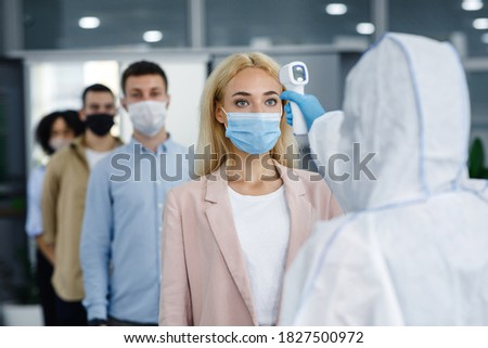 Corporate social distance are new standard to protect health during coronavirus epidemic. Man in hazmat suit with infrared thermometer checks temperature of people in protective masks in office