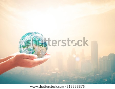 Corporate social responsibility (CSR) concept: Human hands safety holding global earth over blurred big city background. Elements of this image furnished by NASA