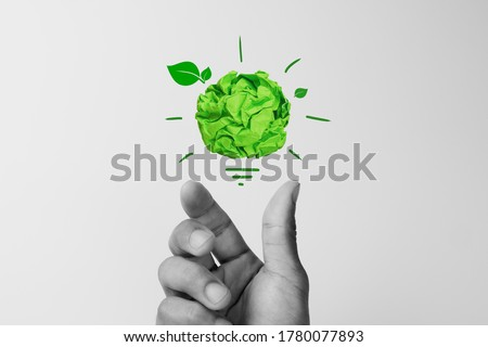 Corporate Social Responsibility(CSR), eco-friendly business concepts with businessman hand holding crumpled green paper light bulb