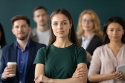 Corporate spirit. Portrait of happy millennial woman new employee worker intern looking at camera starting career having confidence in future proud glad of feeling part of big diverse multiethnic team