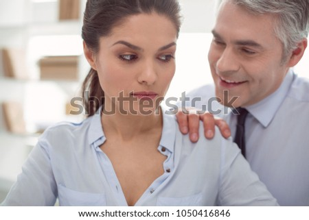 Corporate subordination. Nice moody unhappy woman sitting at the table and listening to her boss while being sexually harassed by him