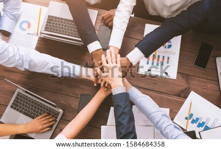 Corporate unity. Multiethnic business team stacking hands together on meeting, top view #1584684358