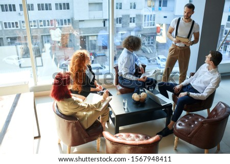 Corporative meeting. Office work and team building. Employees listening to a speaker. A group of 5 caucasian people in the office, two women and 3 men. Top view. Smart and casual business suites. #1567948411