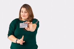 Corpulent blonde haired woman pointing at credit card isolated over grey background. Online payment for purchases, online store, plenty space for ads