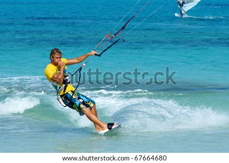 CORRALEJO, FUERTEVENTURA, SPAIN - AUGUST 8: Unknown kitesurfer surfing on a flat azure water of Atlantic ocean on August 8, 2010 in Corralejo, Fuerteventura, Canary islands, Spain