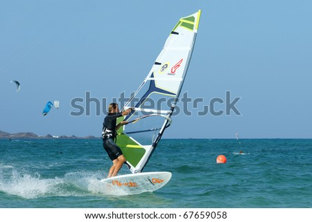 CORRALEJO, FUERTEVENTURA, SPAIN - AUGUST 18: Windsurfer Maurin Rottenwalter making extreme trick on a flat water on August 18, 2010 in Fuerteventura, Canary islands, Spain