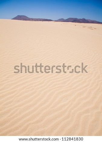 Corralejo sand dunes, extinct volcanoes including montana Roja in the background #112841830