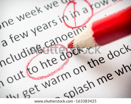 Correcting an essay with red pencil
