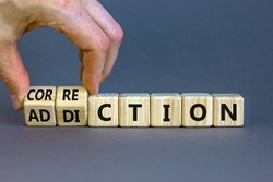 Correction addiction symbol. Businessman turns wooden cubes and changes the word 'addiction' to 'correction'. Beautiful grey background. Business, correction addiction concept. Copy space.