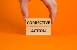 Corrective action symbol. Wooden blocks with words 'Corrective action' on beautiful orange background. Businessman hand. Business and Corrective action concept. Copy space.