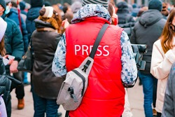 """Correspondent in a red jacket with text """"Press"""" and camera working in crowd. Protest. Strike. City. Outdoor. Job. Professional. Occupation. Specialist. News. Media. Broadcast. TV"""