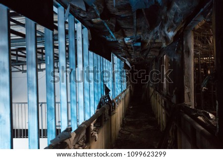 Corridor between rooms of a factory damaged by fire / Damage caused by fire - Burnt interior #1099623299