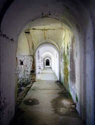 Corridor connecting the military fort in a state of neglect, walls dirty with mold and moss. Forte Leone, Cima Campo, Belluno, Italy