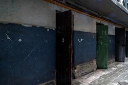 Corridor of former old prison with open wooden doors of cells