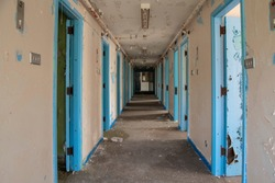Corridor of prison cell doors inside an abandoned prison.