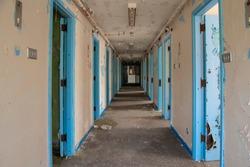 Corridor of prison cell doors inside an abandoned prison.