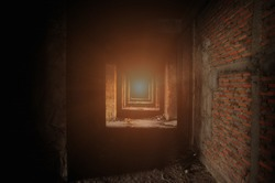 Corridor within the building under construction Also see building structures and red brick walls Which has light from the end of the corridor Makes it look mysterious, but still see the exit far