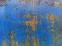 Corroded metal background. Rusted blue painted metal wall. Rusty metal background with streaks of rust. Rust stains. The metal surface rusted spots. Rystycorrosion.