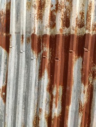 Corroded metal background. Rusted grey painted ribbed metal wall. Rusty metal background with streaks of rust. Rust stains. The metal surface rusted spots. Rystycorrosion.