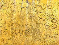 Corroded metal background. Rusted yellow painted metal wall. Rusty metal background with streaks of rust. Rust stains. The metal surface rusted spots. Rystycorrosion.