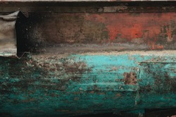 Corroded metal surface with faded and distressed paint layers in turquoise and red.