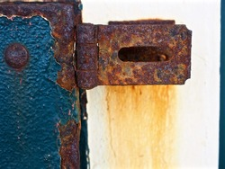 Corroded Rust-Covered Blue Metal Door with Hinge in Weathered Oxidized Condition.