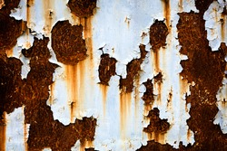 Corroded white metal background. Rusted white painted metal wall. Rusty metal background with streaks of rust. Rust stains. Rysty corrosion.